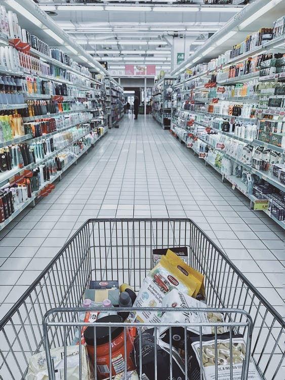 Grocery cart in between store shelves