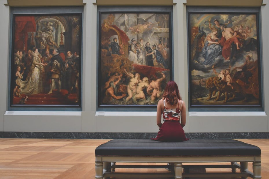 Women sitting in front of paintings at an art museum